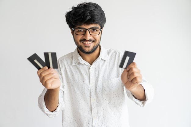 Joyeux confiant jeune détenteur de carte de crédit indien profitant de ses opportunités.