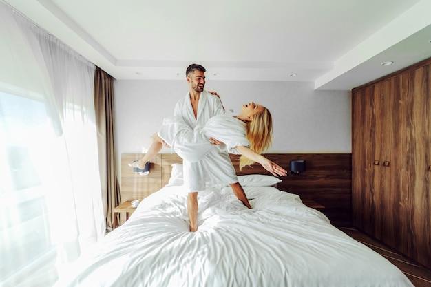 Un joyeux couple d'âge moyen en peignoirs célébrant leur anniversaire dans un hôtel. un homme tenant une femme dans ses mains.