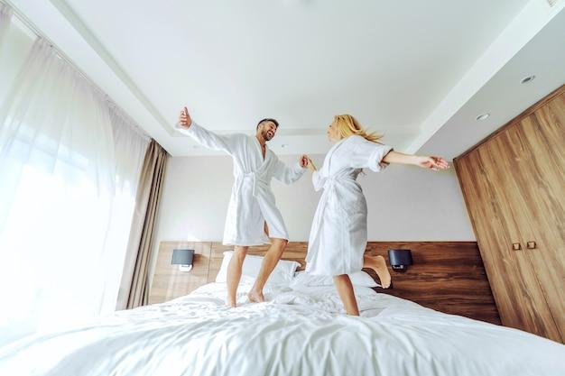Un joyeux couple d'âge moyen en peignoirs célébrant leur anniversaire dans un hôtel le week-end.