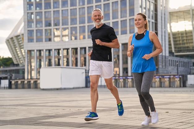 Joyeux couple d'âge mûr homme et femme faisant de l'exercice et du jogging ensemble dans la ville par un été chaud