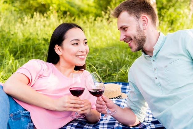 Joyeux couple amoureux portant des verres à vin sur un pique-nique dans la nature