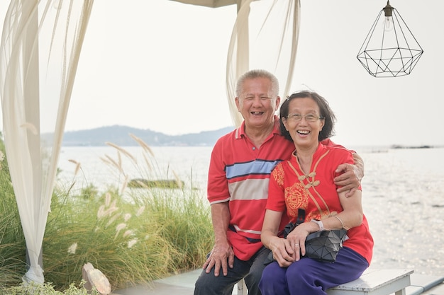 Joyeux couple asiatique âgé se reposant au bord de la mer par une journée ensoleillée, concept de bonne retraite, voyage pour le concept de vacances du nouvel an lunaire chinois