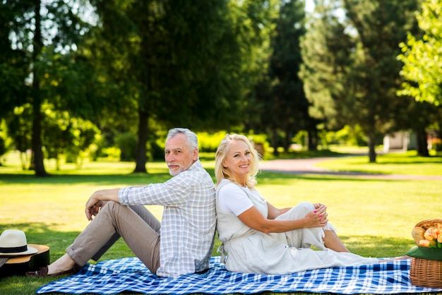 Joyeux couple assis dos à dos
