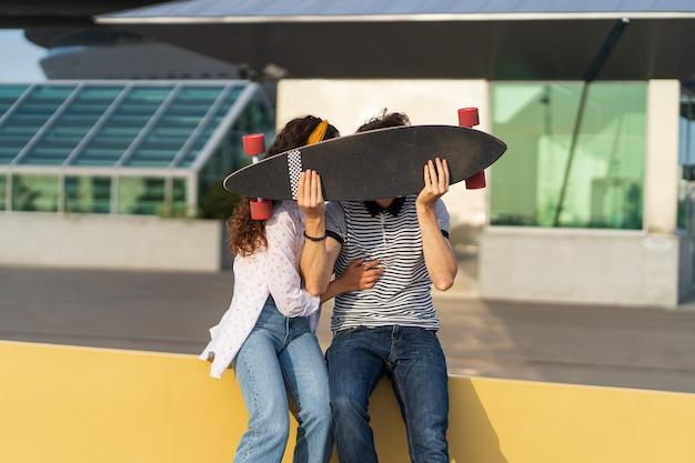 Joyeux couple baiser se cachant au-dessus de longboard espiègle homme et femme amoureux ensemble tenir skateboard
