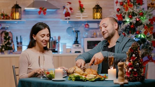 Joyeux couple célébrant le réveillon de noël avec un dîner de fête