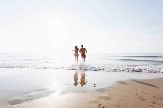 Joyeux couple en cours d'exécution sur le rivage