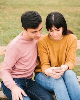 Joyeux couple dans le parc en regardant téléphone