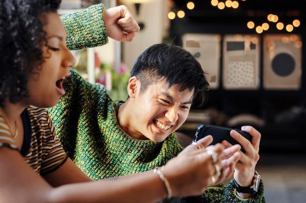 Joyeux couple jouant à un jeu en ligne sur leurs téléphones