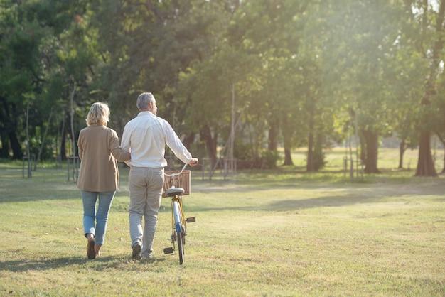 Joyeux couple de personnes âgées actives avec vélo marchant ensemble dans le parc. des activités parfaites pour les personnes âgées en retraite.