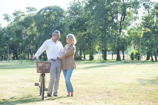Joyeux couple de personnes âgées actives avec vélo marchant ensemble dans un parc public