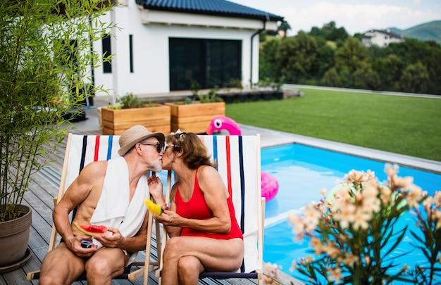 Joyeux couple de personnes âgées amoureux assis au bord de la piscine à l'extérieur dans la cour, s'embrassant.