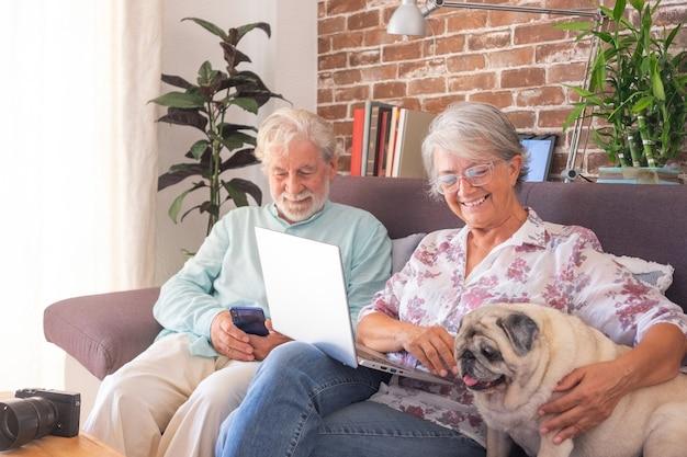 Joyeux couple de personnes âgées assis sur un canapé à la maison avec leur vieux chien carlin, utilisant un ordinateur et un téléphone portable.