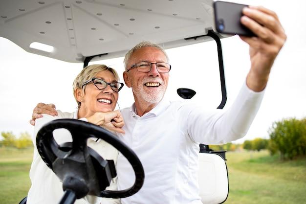 Joyeux couple de personnes âgées en buggy de golf prenant une photo avant les loisirs et profitant du temps libre à l'extérieur.