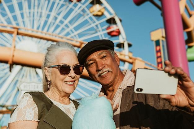 Joyeux couple de personnes âgées prenant un selfie avec de la barbe à papa à pacific park à santa monica, californie