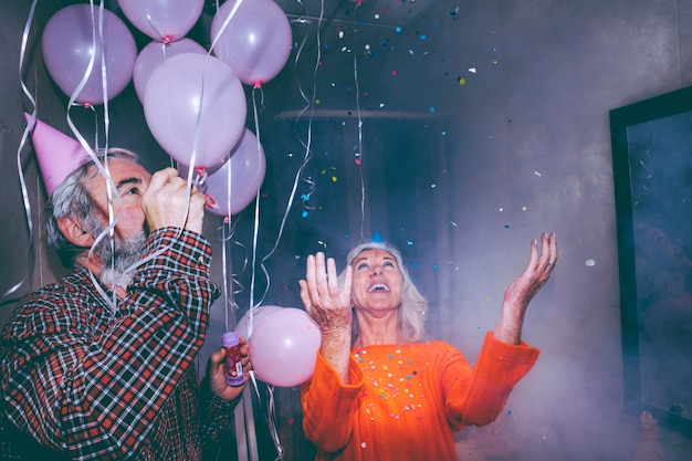 Joyeux couple de personnes âgées profitant de la fête