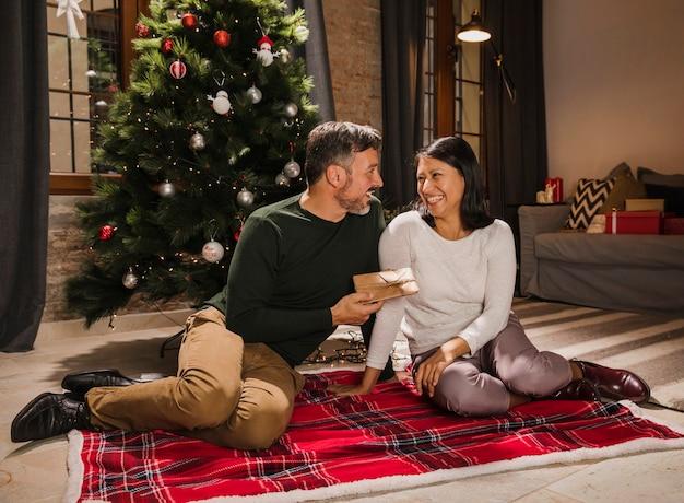 Joyeux couple de personnes âgées souriant et offrant des cadeaux les uns aux autres