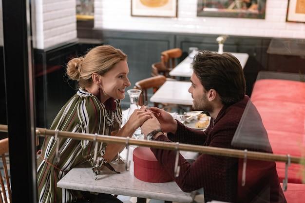 Joyeux couple positif parlant et main dans la main