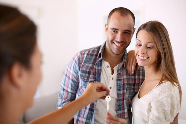 Joyeux couple prenant les clés de leur nouvelle maison