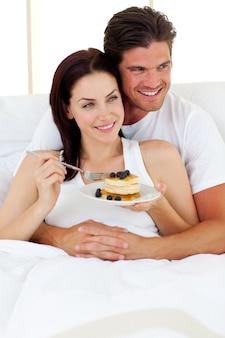 Joyeux couple prenant son petit déjeuner