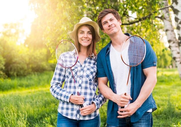 Joyeux couple avec des raquettes de badminton dans le parc