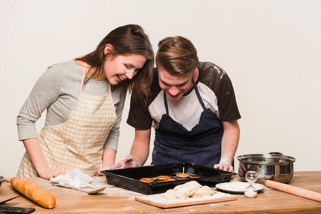 Joyeux couple regardant des anneaux de pâtisserie