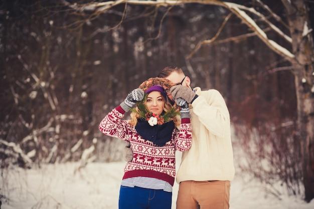 Joyeux couple s'amusant dans les bois d'hiver
