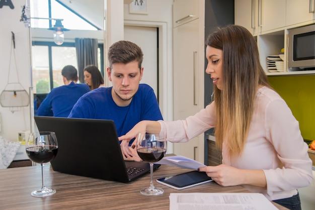 Joyeux couple se détendent et travaillent sur un ordinateur portable à la maison d'intérieur de la cuisine moderne. un couple d'âge moyen travaillant à la maison