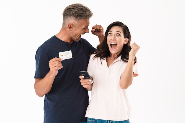 Joyeux couple séduisant portant une tenue décontractée debout isolé sur un mur blanc, faisant des achats en ligne avec un téléphone portable et une carte de crédit
