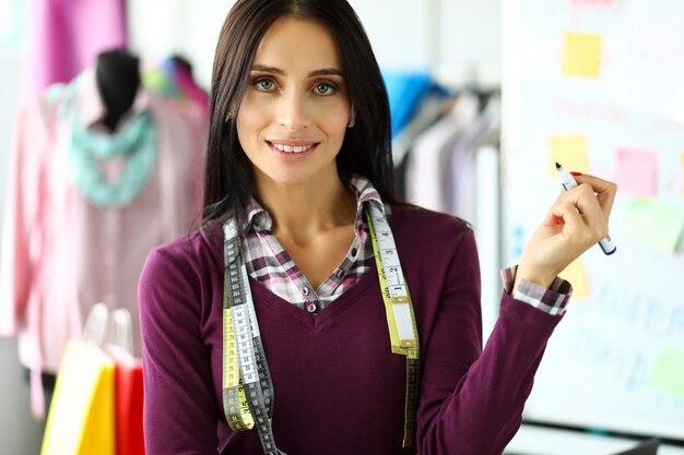 Joyeux créateur de mode féminine tenant dans les bras tableau blanc marqueur