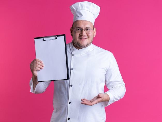 Joyeux cuisinier mâle adulte portant un uniforme de chef et des lunettes regardant à l'avant montrant le presse-papiers pointant avec la main dessus isolé sur un mur rose