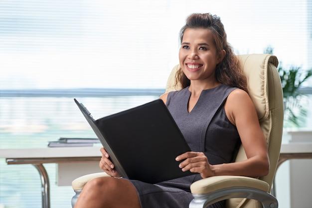 Joyeux directeur des ressources humaines avec dossier manquant assis à l'entretien d'embauche et regardant de côté