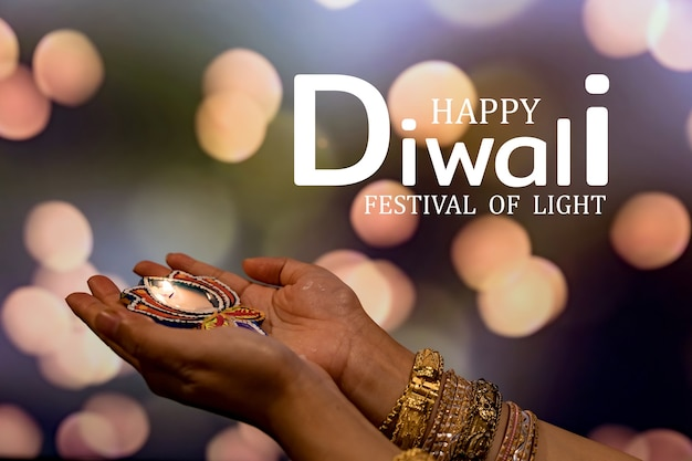 Joyeux diwali - mains de femme au henné tenant une bougie allumée isolée sur fond sombre. lampes en argile diya allumées pendant dipavali, fête hindoue des lumières. copiez l'espace pour le texte.