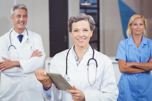 Joyeux docteur tenant une tablette numérique tandis que ses collègues avec les bras croisés