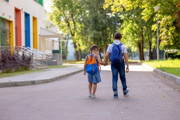 Joyeux écoliers une petite fille et un garçon dans une chemise blanche avec des sacs à dos vont sur le chemin de