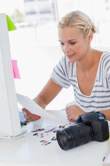 Joyeux éditeur de photos en regardant une feuille de contact