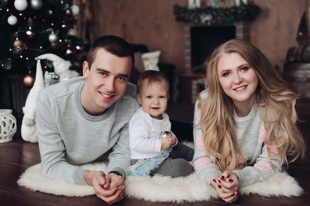 Joyeux embrassant parents et bébé parmi les cadeaux de noël