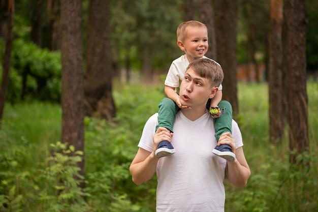 Joyeux enfant drôle à cheval sur les épaules des papas papa et fils de race blanche jouant ensemble