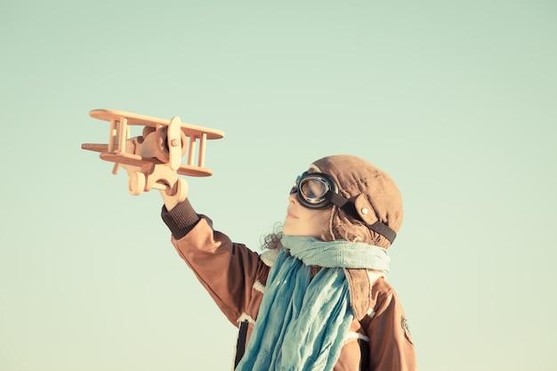 Joyeux enfant jouant avec un avion en bois jouet sur fond de ciel d'automne. rétro tonique