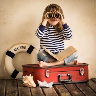 Joyeux enfant jouant avec un voilier jouet à l'intérieur. concept de voyage et d'aventure