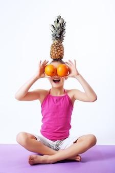 Joyeux enfant avec des oranges, des ananas et des bananes.