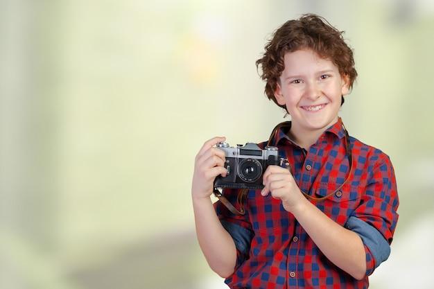 Joyeux enfant souriant (garçon) tenant une caméra instantanée