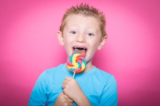 Joyeux enfant souriant avec une sucette sucrée s'amusant sur une surface rose colorée