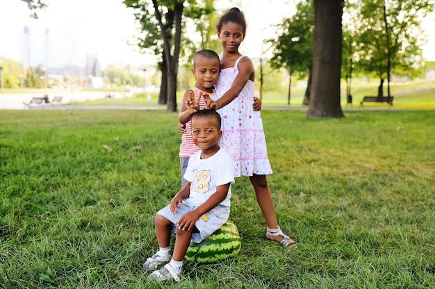 Joyeux enfants afro-américains noirs jouant avec une grosse pastèque dans le parc sur l'herbe et souriant.