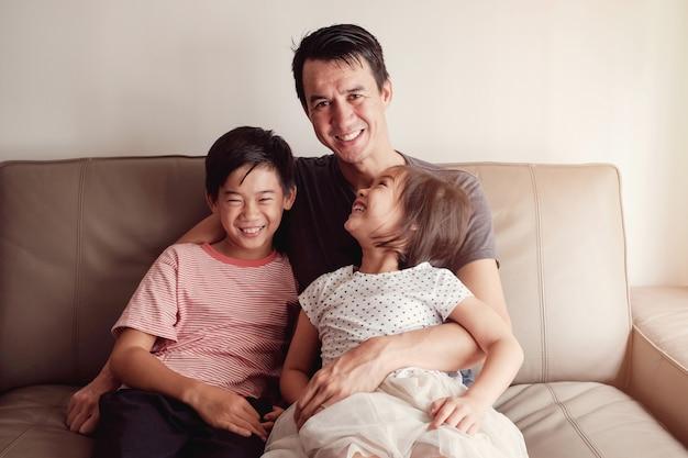 Joyeux enfants asiatiques multiculturels avec leur père à la maison