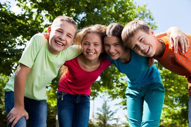 Joyeux enfants divers souriants s'embrassant dans le parc