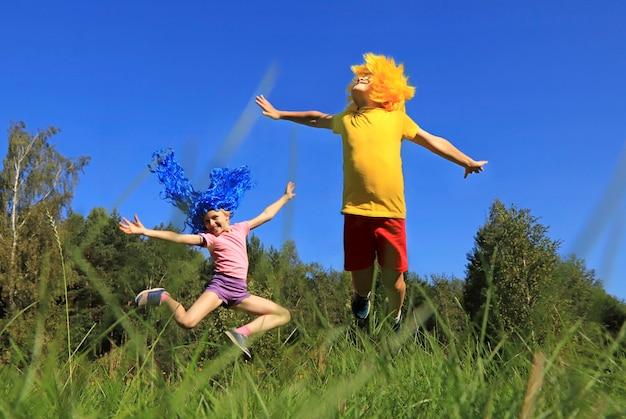 Joyeux enfants garçon et fille aux cheveux bleus et jaunes sautant sur la pelouse dans la nature près de la forêt par temps ensoleillé.