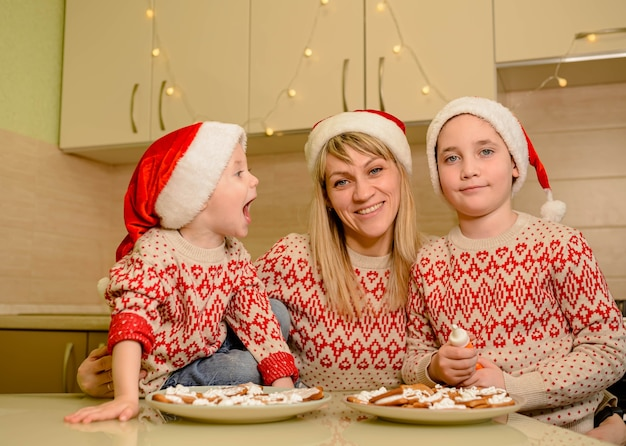 Joyeux enfants garçons décorant des biscuits de pain d'épice avec plaisir