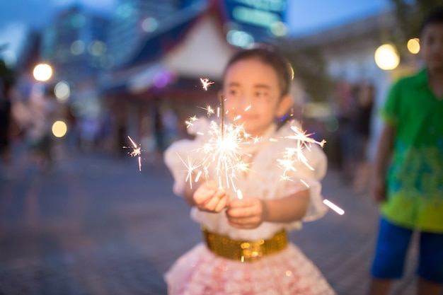 Joyeux enfants jouant avec des feux d'artifice.