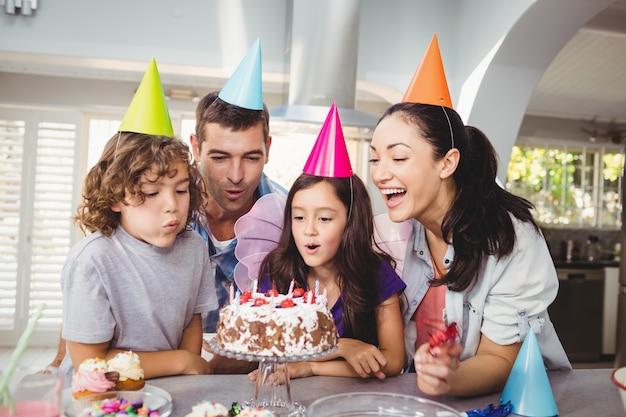 Joyeux enfants soufflant des bougies sur le gâteau d'anniversaire
