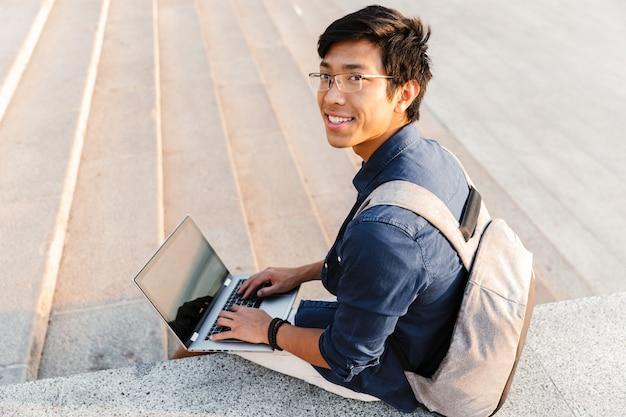 Joyeux étudiant asiatique avec sac à dos à l'aide d'un ordinateur portable alors qu'il était assis à l'extérieur